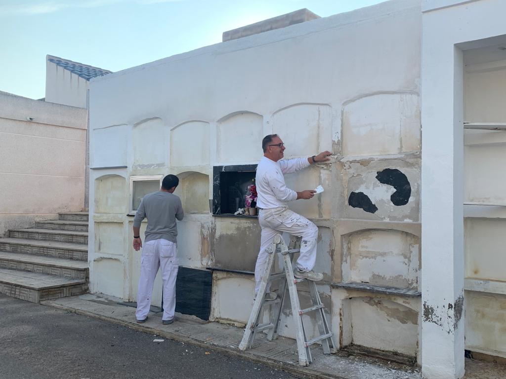 Imagen de los pintores arreglando algunas paredes del cementerio